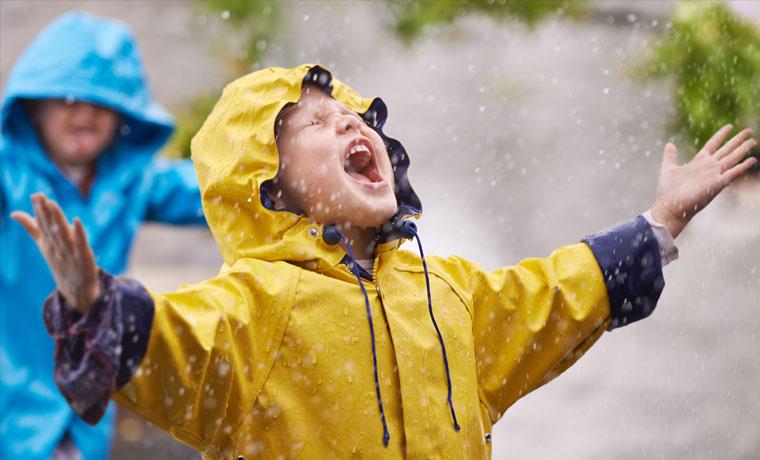 Niño disfrutando bajo la lluvia.