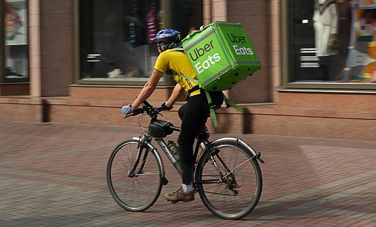 Repartidor de UBER EATS realizando una entrega en bicicleta