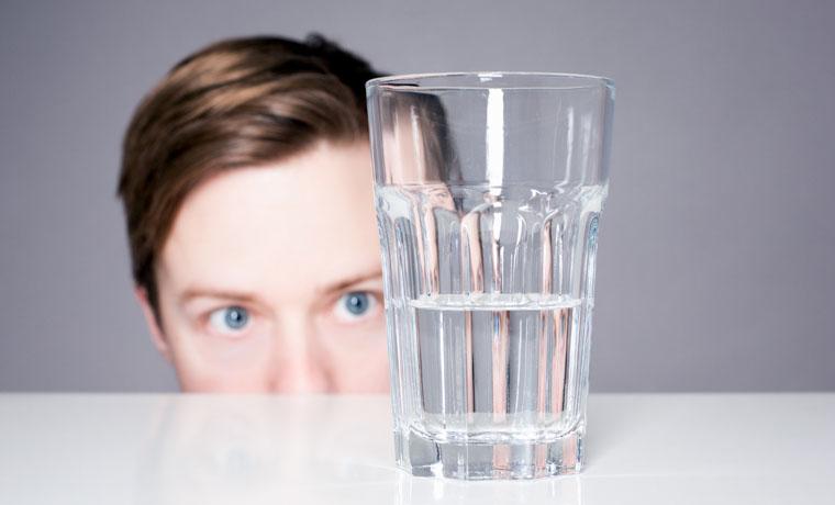 Hombre valorando si el vaso está medio lleno o medio vacío