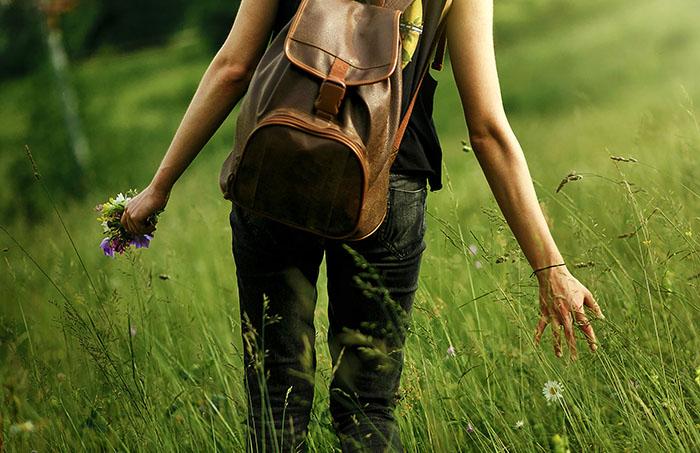 Mujer acariciando la hierba alta en un paseo por el campo